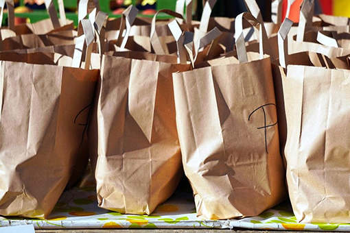 Table of brown paper bags with unknown contents depicting emergency packs