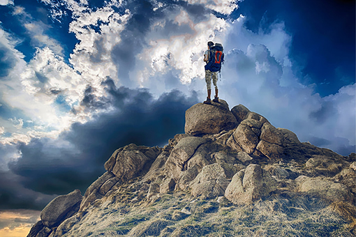 Image of a man standing at the top of a mountain