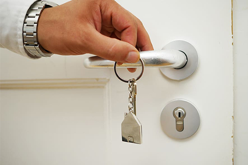 Image of mans hand holding up keyring to door